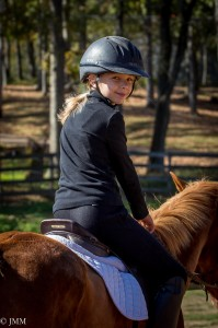 Young girl in helmet riding a chestnut pony.